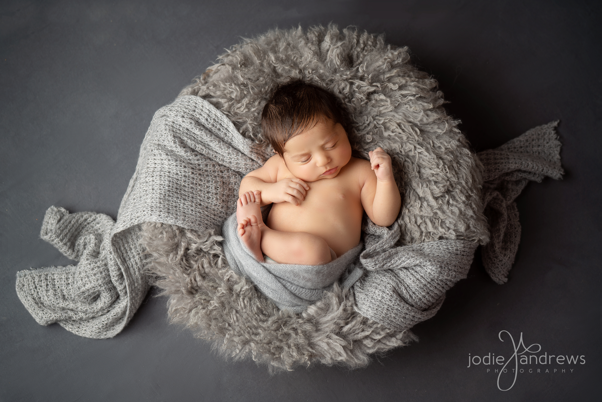 Baby Newborn Boy On Grey Background with Grey Wrap and float