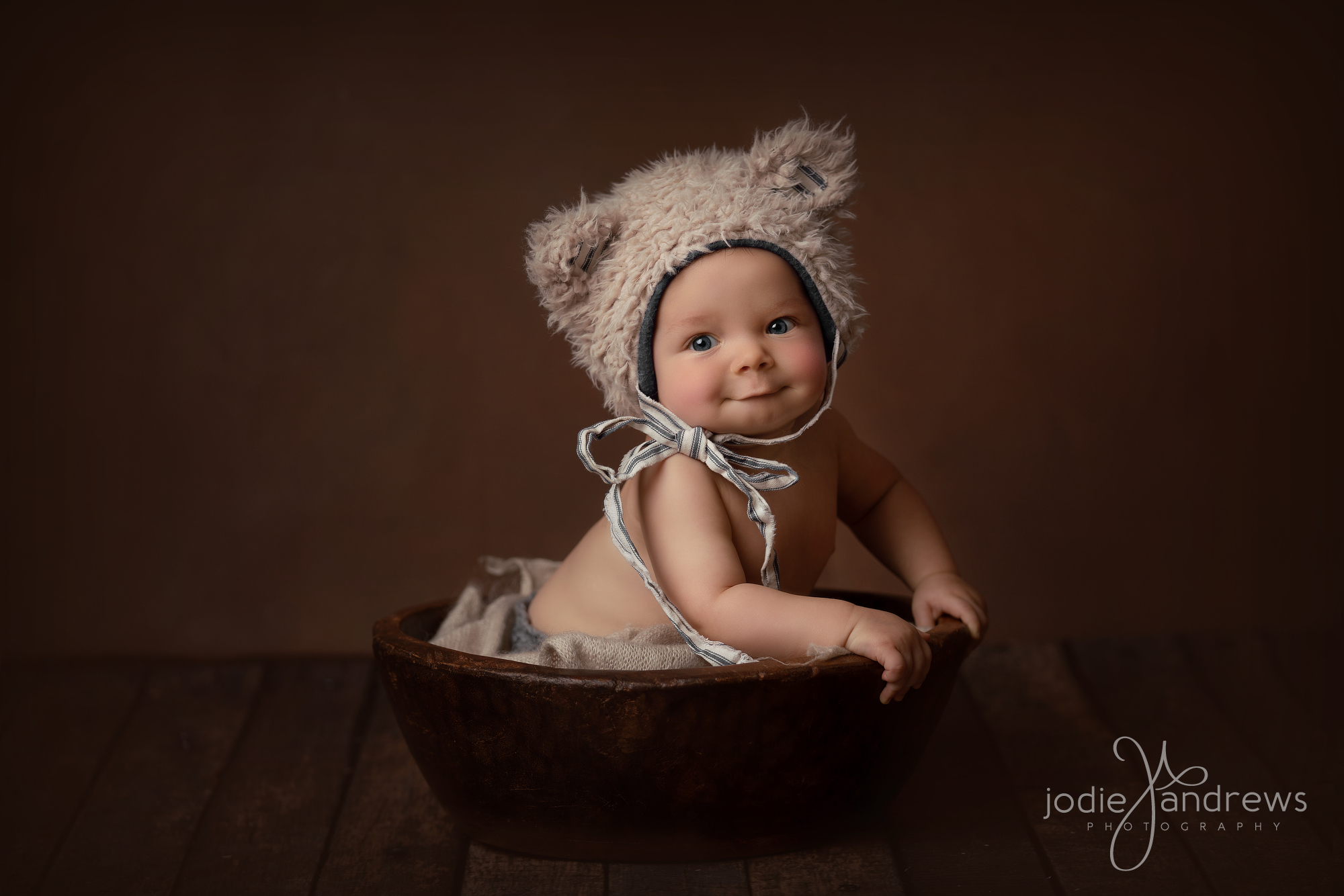 Cute Baby Boy sitting in bowl on brown background with bear hat on